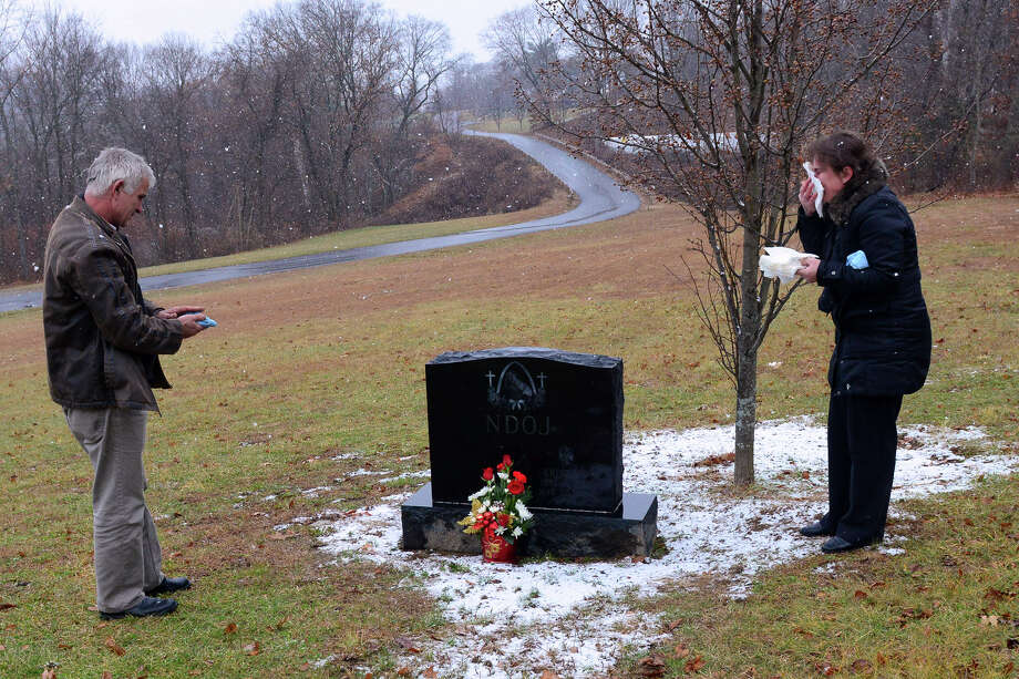 Fran Ndoj and his wife Rudina Ndoj visit the grave of their son Kristjan at Mount St. Peter Cemetery in Derby, Conn., on Sunday Dec. 21, 2014. Kristjan died March 20, 2014, five days after being shot while standing outside a friend's home. Photo: Christian Abraham / Connecticut Post