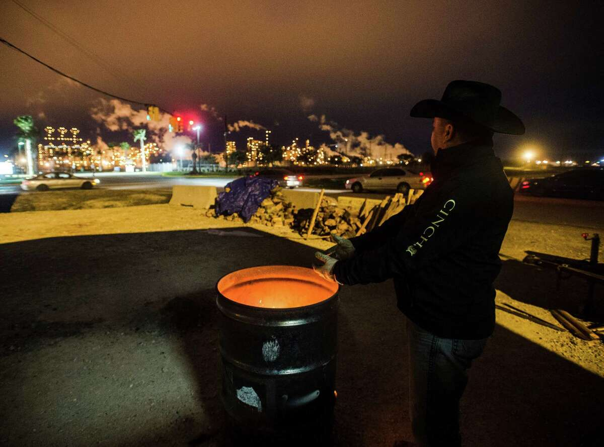 Troy Deriso warms his hands over a fire barrel as he and others man the strike outside the Motiva Enterprises plant in Port Arthur on Wednesday. Striking workers in Port Arthur maintained their picket lines throughout the chill of Wednesday night, pacing across several access roads to Motiva Enterprises. Photo taken Wednesday 2/25/15 Jake Daniels/The Enterprise