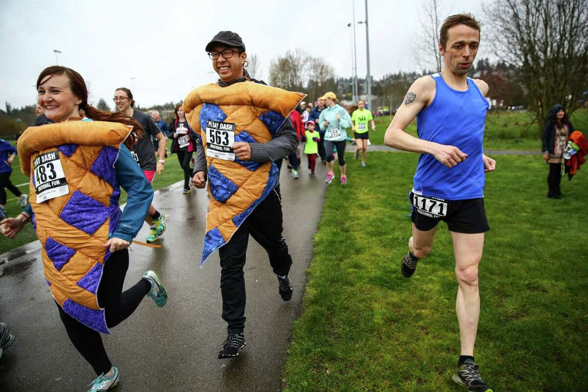 Melissa Brown and Steven Chau run while dressed as slices of pie during the Pi Day Dash at Magnuson Park. Hundreds of people competed in the 3.14 mile race, ate pie, competed in a pie-eating contest and threw whipped cream pies at their friends. The race started at 9:26, on March 14th, or 3/14/15 9:26. The first number of the mathematical constant Pi are 3.1415926... The event raised money for the Leukemia & Lymphoma Society. Photographed on Pi Day, Saturday, March 14, 2015.