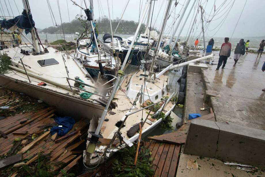 In this image provided by UNICEF Pacific, people on a dock view yachts damaged in Port Vila, Vanuatu, Saturday, March 14, 2015, in the aftermath of Cyclone Pam. Winds from the extremely powerful cyclone that blew through the Pacific's Vanuatu archipelago are beginning to subside, revealing widespread destruction. (AP Photo/UNICEF Pacific, Humans of Vanuatu) EDITORIAL USE ONLY, NO SALES Photo: HONS / UNICEF Pacific