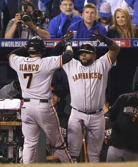 Giants Pablo Sandoval greets Gregor Blanco in the dugout after Blanco hit a home run in the first inning during Game 2 of the World Series at Kauffman Stadium on Wednesday, Oct. 22, 2014 in Kansas City, Mo.