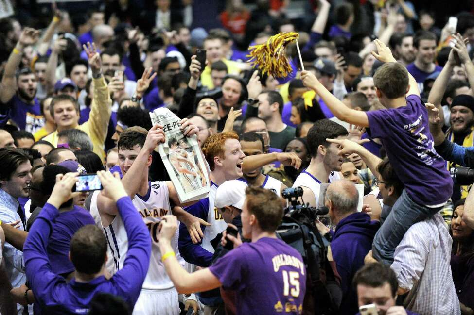 UAlbany players celebrate with fans on the floor after a thrilling 51-50 win over Stony Brook during their America East Championship game on Saturday, March 13, 2015, at UAlbany. Hooley hit a 3-point buzzer-beater to win the game. (Cindy Schultz / Times Union)