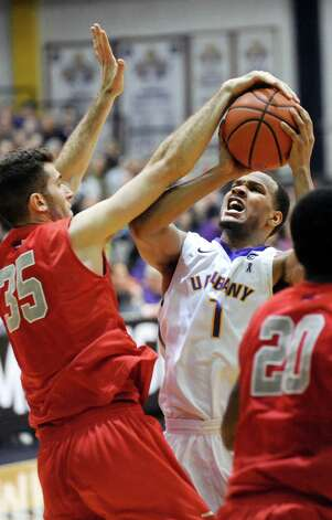 UAlbany's Ray Sanders, center, looks to the hoop as Stony Brook's Scott King defends during their America East Championship game against Stony Brook on Saturday, March 13, 2015, at UAlbany in Albany, N.Y. (Cindy Schultz / Times Union) Photo: Cindy Schultz / 00030954A