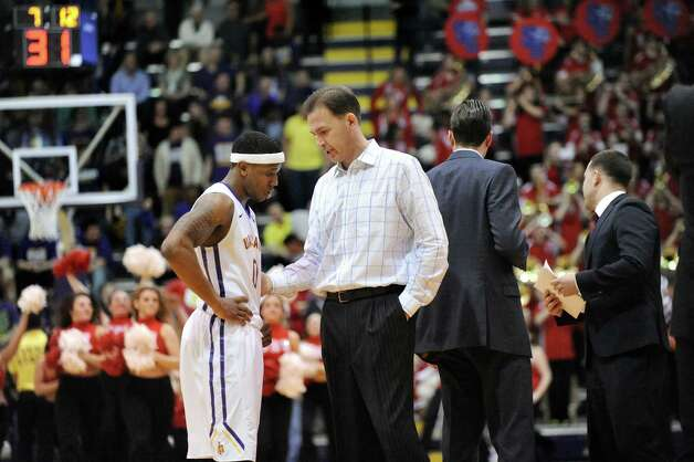 UAlbany's coach Will Brown, center, checks in with Evan Singletary, left, during a time out in their America East Championship game against Stony Brook on Saturday, March 13, 2015, at UAlbany in Albany, N.Y. (Cindy Schultz / Times Union) Photo: Cindy Schultz / 00030954A