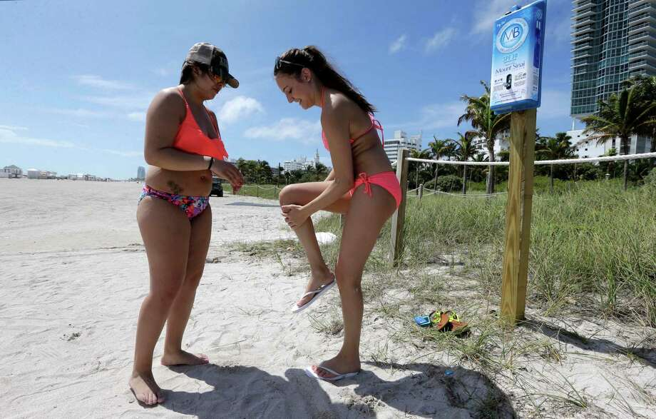 Sara Larsen, of Minnesota, left, and Nicolette Sansone, of Illinois, apply sunscreen at the beach, Friday, March 13, 2015, in Miami Beach, Fla. The City of Miami Beach is celebrating its centennial on March 26, installing 50 sunscreen dispensers throughout the city for public use as a birthday gift to the community. (AP Photo/Alan Diaz) Photo: Alan Diaz, STF / AP