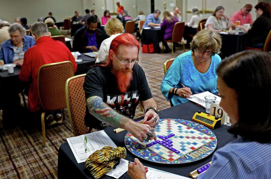 Henry Moses, center, of San Antonio, squares off Saturday against Houstonian Deanne Dorsa in the 2015 Houston Open Scrabble Tournament at the Houston Marriott North. Photo: Gary Coronado, Staff / © 2015 Houston Chronicle