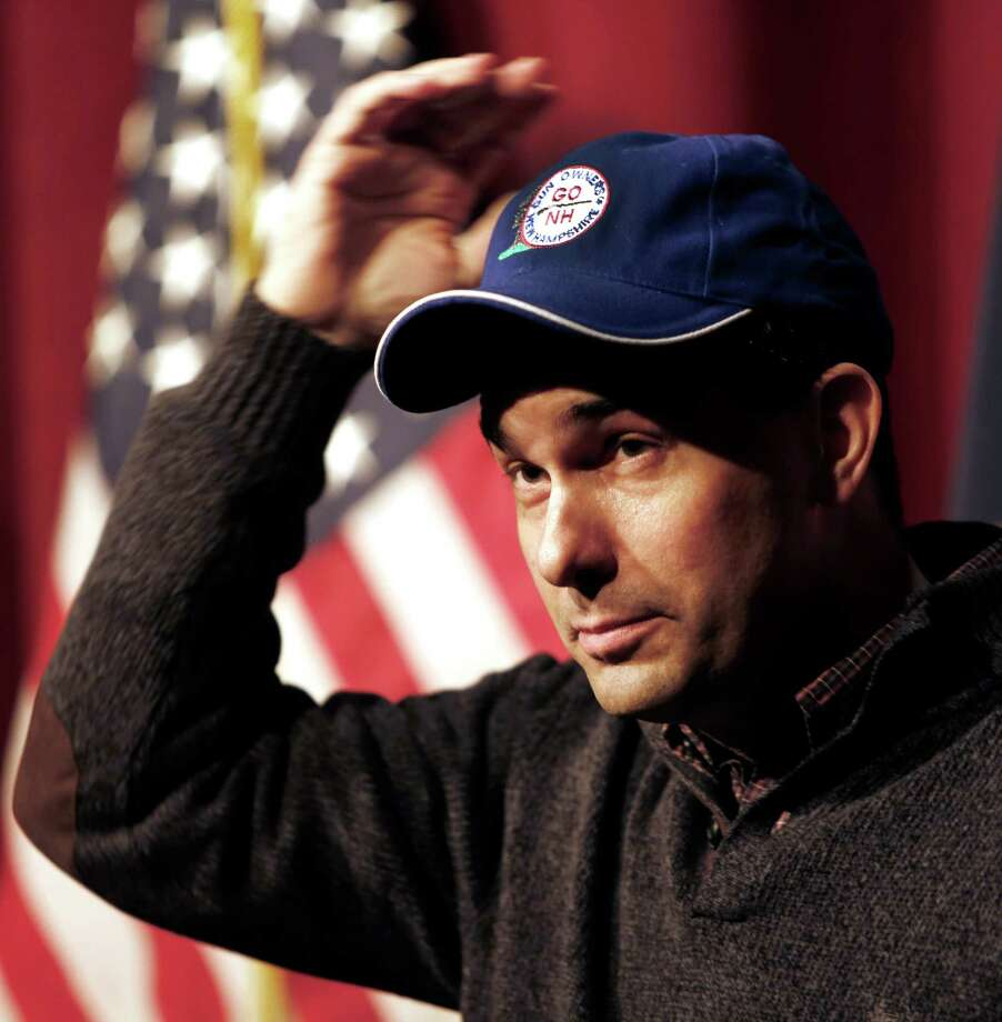 Wisconsin Gov. Scott Walker puts on a cap given to him by a member of the New Hampshire Gun Owners Association while answering questions at a training workshop for the New Hampshire state Republican Party in the auditorium at Concord High School Saturday, March 14, 2015, in Concord, N.H. (AP Photo/Jim Cole) Photo: Jim Cole, STF / AP