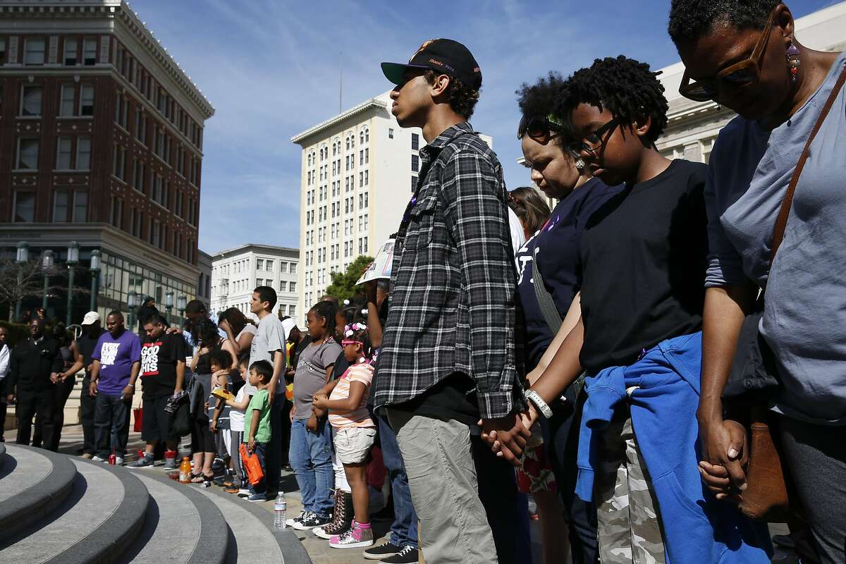 Community members, family and friends hold hands and pray during a community dance party organized not only to honor Chyemil Pierce and other people killed by violence in Oakland, but also to celebrate life in Frank H. Ogawa Plaza March 14, 2015 in Oakland, Calif.