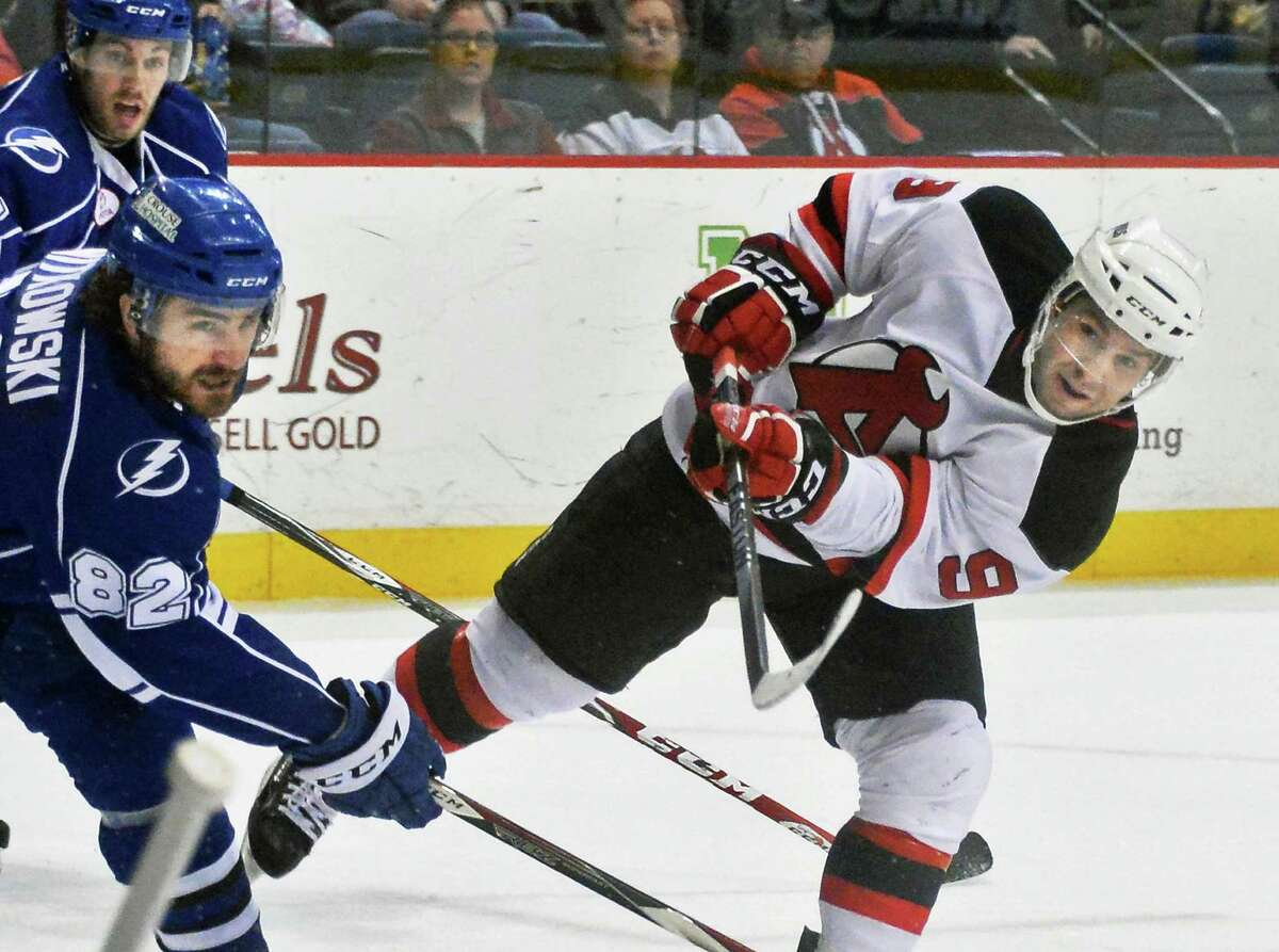 Albany Devils's # 9 Joe Whitney, right, gets off a shot on goal against the Syracuse Crunch at the Times Union Center Saturday March 14, 2015 in Albany, NY. (John Carl D'Annibale / Times Union)