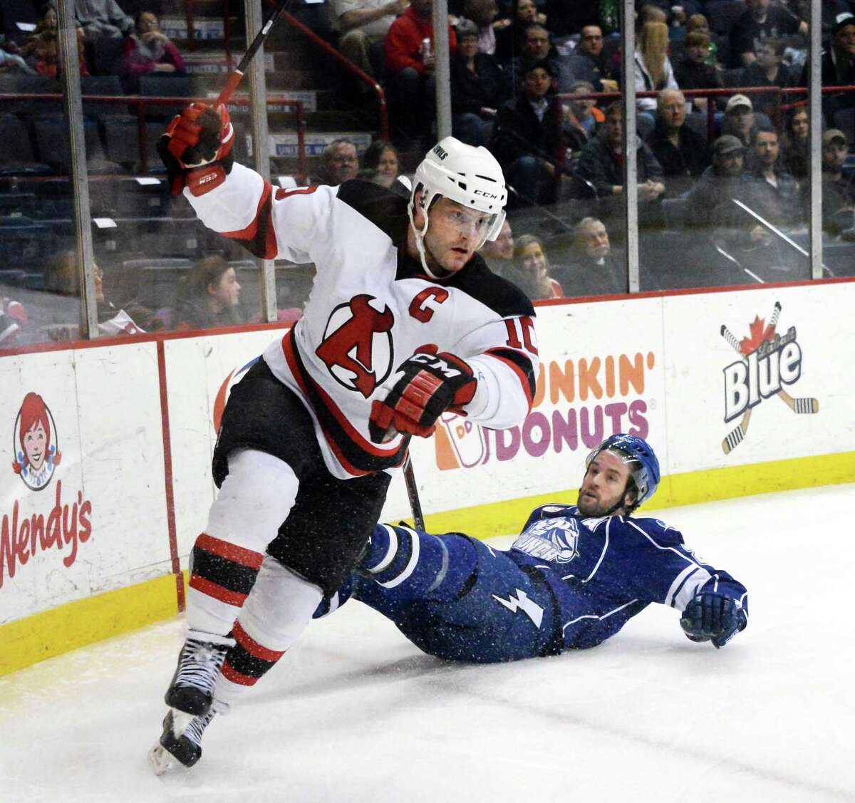 Albany Devils's # 10 Rod Pelley, left, skates away after hard check to Syracuse Crunch's #24 Jean-Philippe Cote during Saturday's game at the Times Union Center March 14, 2015 in Albany, NY. (John Carl D'Annibale / Times Union)