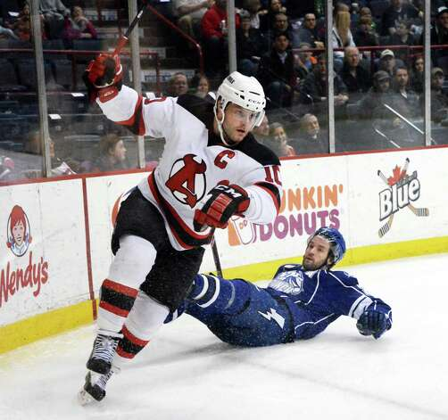 Albany Devils's # 10 Rod Pelley, left, skates away after  hard check to Syracuse Crunch's #24 Jean-Philippe Cote during Saturday's game at the Times Union Center  March 14, 2015 in Albany, NY.  (John Carl D'Annibale / Times Union) Photo: John Carl D'Annibale / 00030124L
