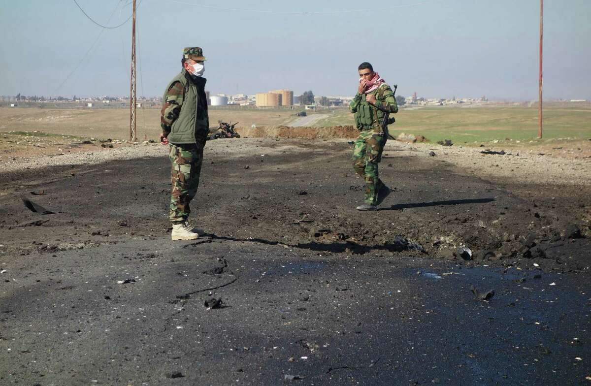In this undated photo made avaialble Saturday, March 14, 2015, by the Kurdistan Region Security Council (KRSC), Kurdish soldiers survey the site of a bomb attack on a road between Mosul, Iraq, and the Syrian border in northern Iraq. Kurdish authorities in Iraq said Saturday they have evidence that the Islamic State group used chlorine gas as a chemical weapon against peshmerga fighters, the latest alleged atrocity carried out by the extremist organization now under attack in Tikrit. (AP Photo/Kurdistan Region Security Council) ORG XMIT: CAIHK127