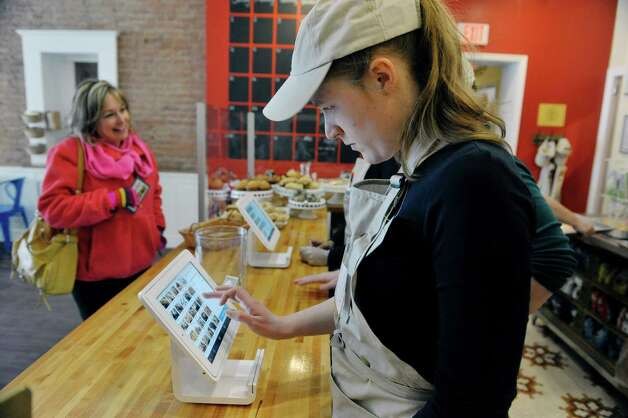 Puzzles Bakery and Cafe employee Anne Cushing uses a ordering terminal as she goes through training on Thursday, March 12, 2015, in Schenectady, N.Y.   (Paul Buckowski / Times Union) Photo: PAUL BUCKOWSKI / 00030979A