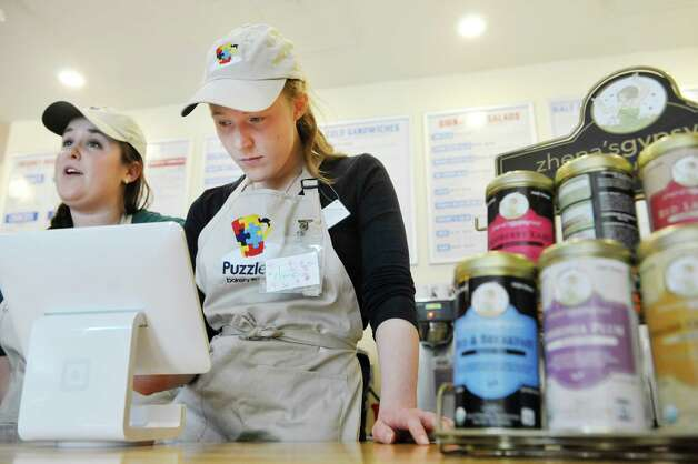 Sara Mae Hickey, left, owner of Puzzles Bakery and Cafe trains employee Anne Cushing on using the ordering terminal on Thursday, March 12, 2015, in Schenectady, N.Y.   (Paul Buckowski / Times Union) Photo: PAUL BUCKOWSKI / 00030979A
