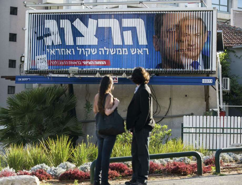 A campaign billboard rotates images of Prime Minister Benjamin Netanyahu, right, with his opponent, MP Labour Party leader Isaac Herzog, in Tel Aviv. Photo: JACK GUEZ, Staff / AFP PHOTO / JACK GUEZ