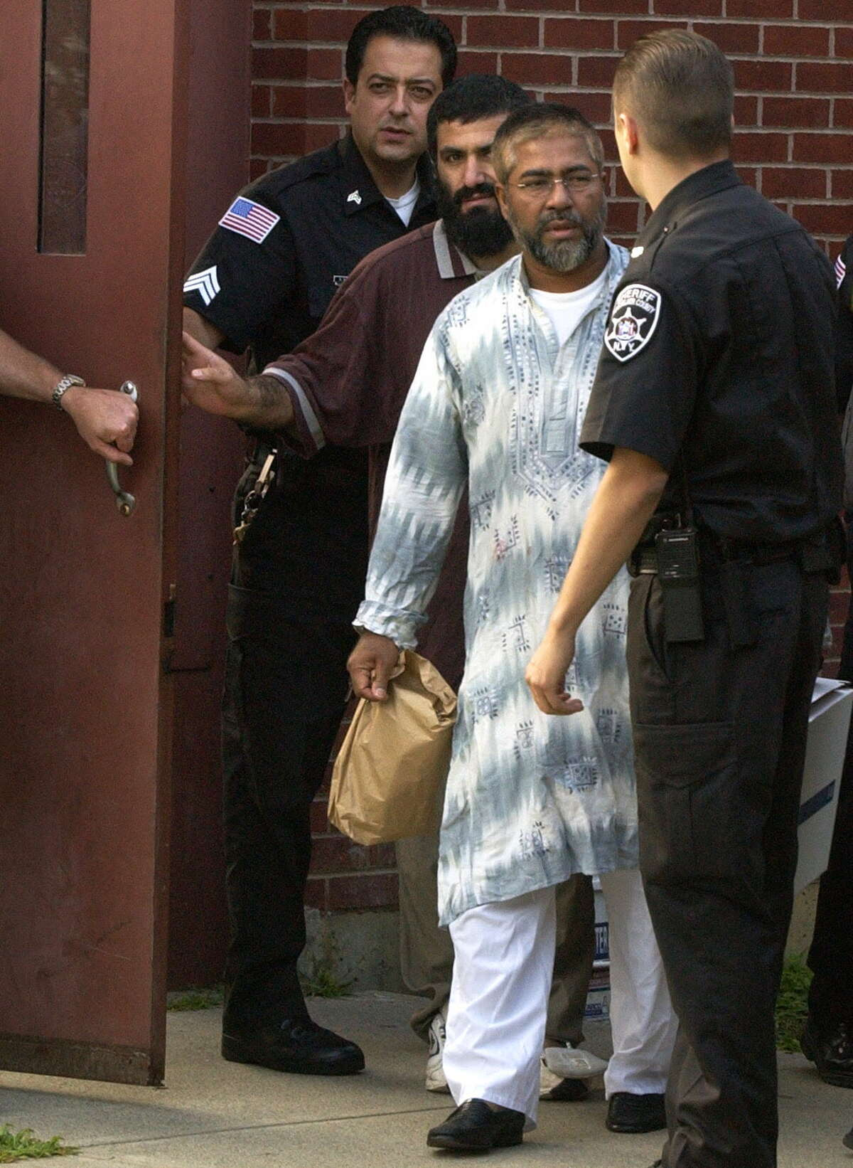 Yassin Muhiddin Aref, left, and Mohammed Mosharref Hossain, right, are released on bail from the Rensselaer County Jail, Wednesday, Aug. 25, 2004. (Will Waldron/Times Union archive)