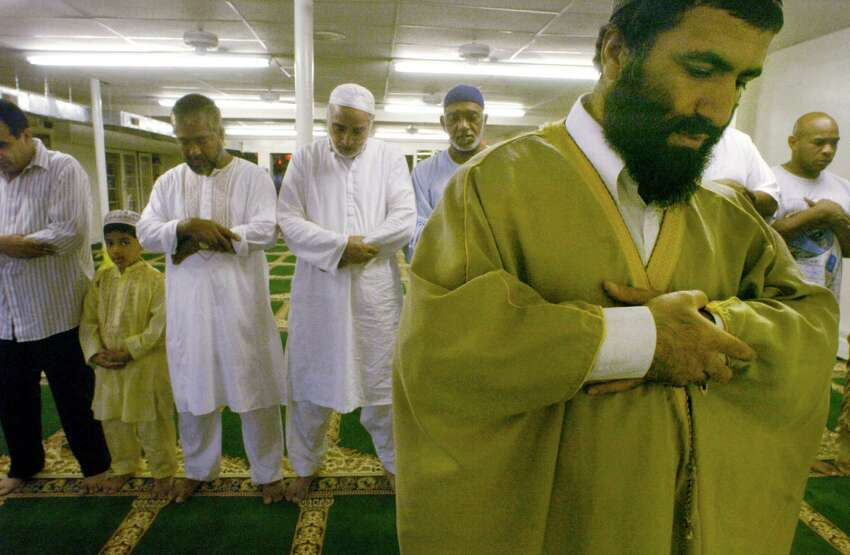 Yassim Muhiddin Aref, front right, and Mohammed Hossain, third from left, with his eight-year-old son Horyra, worship during a mid-day prayer at the Masjid As-Salam Mosque on Central Ave. Thursday, Sept. 2, 2004, in Albany, N.Y. (Michael P. Farrell/Times Union archive)