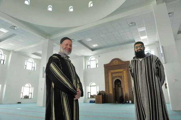 Imams Djafer Sebkhaoui, left, and Arsalan Haque, right, pose for a photograph inside the prayer hall at the Al-Hidaya Center on Wednesday, March 11, 2015, in Latham, N.Y.  (Paul Buckowski / Times Union) Photo: PAUL BUCKOWSKI / 00030978A