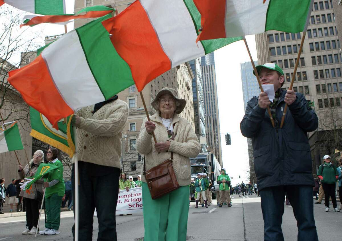 Members of the Flanagan family wave Irish flags while parading down 4th Ave. for the annual St. Patrick's Day Parade in downtown Seattle. Photographed on Saturday, March 14, 2015.