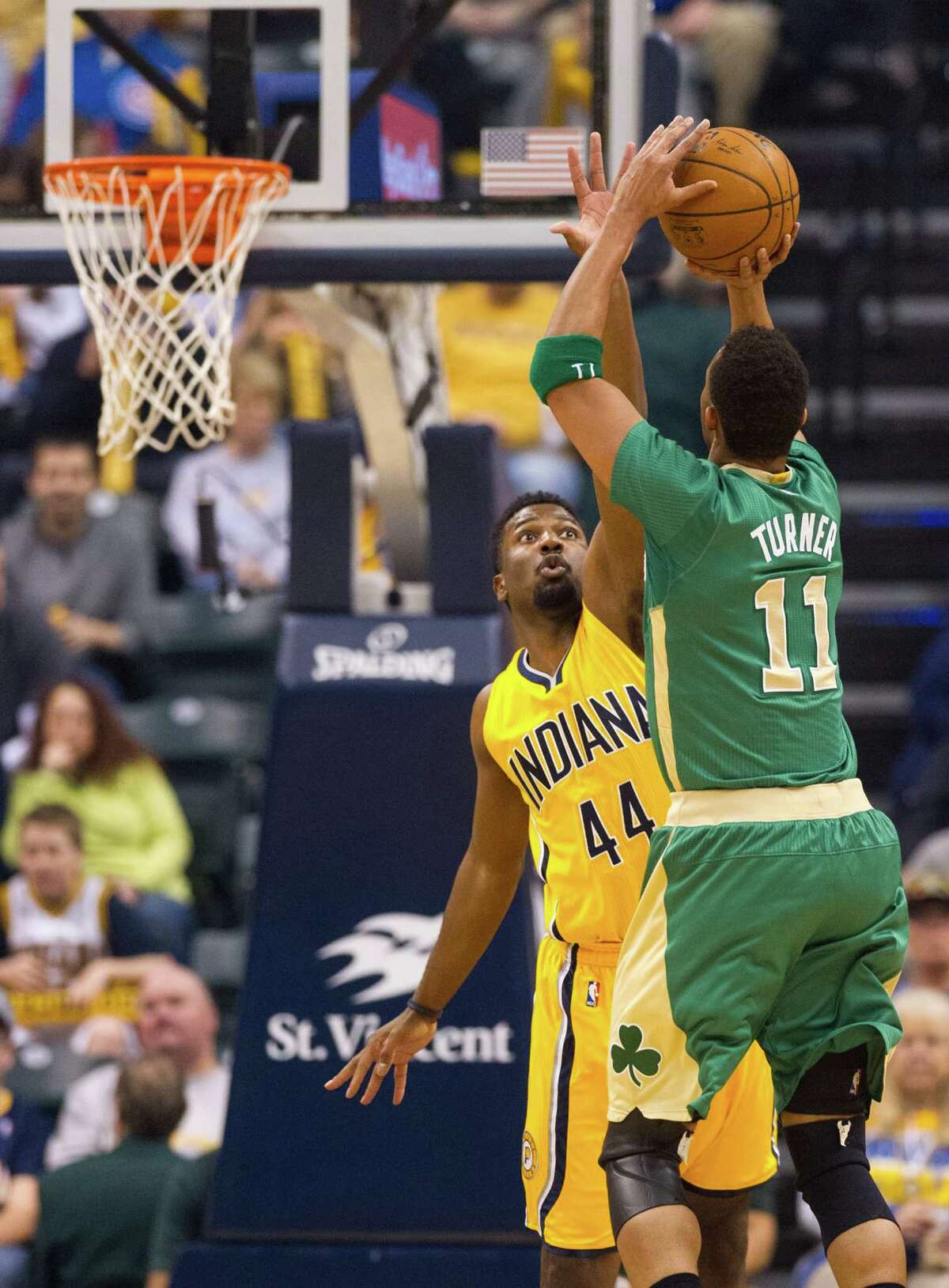 Boston Celtics guard Evan Turner (11) gets a shot off over the defense of Indiana Pacers forward Solomon Hill (44) during the first half of an NBA basketball game, Saturday, March 14, 2015, in Indianapolis. (AP Photo/Doug McSchooler) ORG XMIT: NAF102