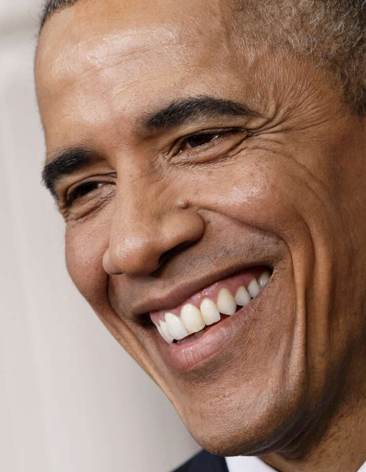 """File-This Dec. 19, 2014, file photo shows President Barack Obama smiling during a news conference in the Brady Press Briefing Room of the White House in Washington. """"Next week I'm signing an executive order to get off my law,"""" Obama joked Saturday, March, 14, 2015, at the Gridiron Club and Foundation's annual dinner. On top of that, the nation's graying chief executive says he's having trouble now with his morning cup of joe. """"Coffee really disagrees with me these days,"""" he says, """"which is why John Boehner just invited coffee to address the joint House."""" (AP Photo/J. Scott Applewhite, File) Photo: J. Scott Applewhite, STF / AP"""