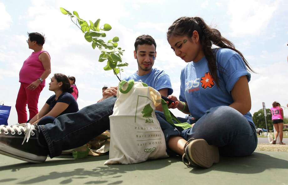Earth Day comes March 22. It should be a time to reflect on the need to respect God's creation. Ailyn Duran (right) and Jacob De Hoyos sit with their Redbud plant at the Earth Day Fiesta celebration at Woodlawn Lake in 2014. Photo: Kin Man Hui /San Antonio Express-News / ©2014 San Antonio Express-News