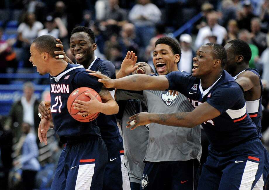 Connecticut players celebrate after defeating Tulsa 47-42 in an NCAA college basketball game in the semifinals of the American Athletic Conference tournament in Hartford, Conn., on Saturday, March 14, 2015. Photo: Fred Beckham, AP / FR153656 AP
