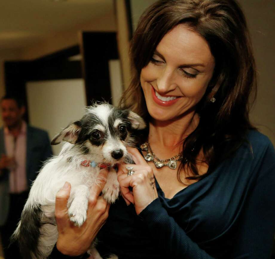"Kate Smargiasso pets Diego at Petopia's inaugural ""We Don't Do Phaux Paw"" fashion event at JW Marriott downtown. Photo: Jon Shapley, Houston Chronicle / © 2015 Houston Chronicle"