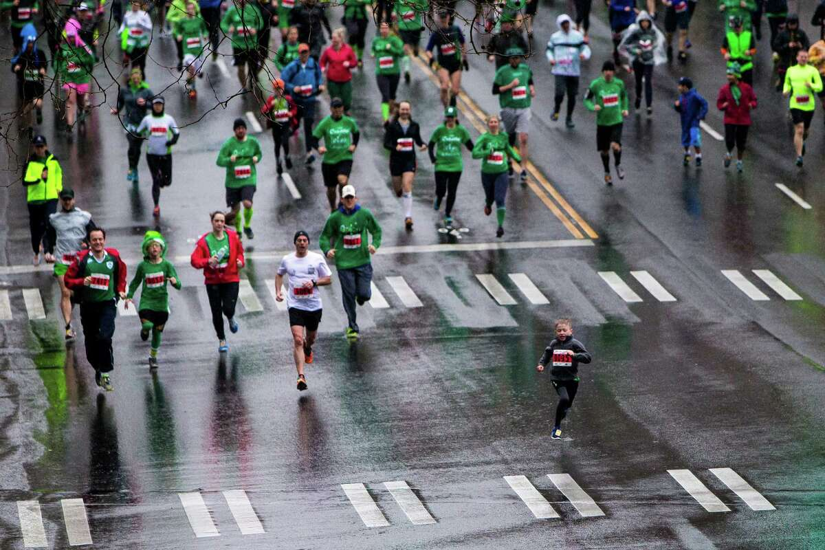 A young man leads a wave of runners at the annual St. Patrick's Day Dash Sunday, March 15, 2015, in Seattle, Washington. The event benefits the Detlef Schrempf Foundation.