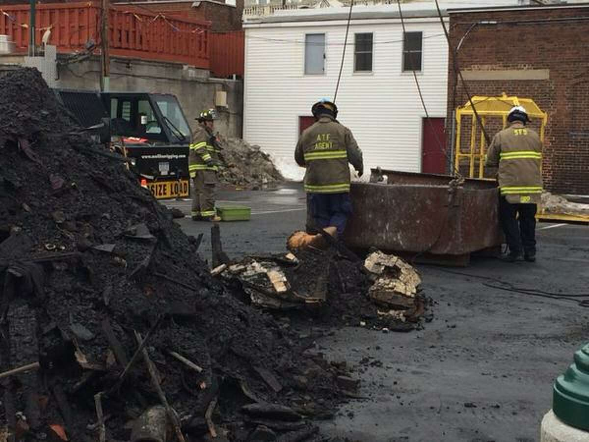 Members of the federal Bureau of Alcohol, Tobacco, Firearms and Explosives and other fire officials prepare to lower a load of fire debris taken from 104 Jay Street in Schenectady March 15, 2015.