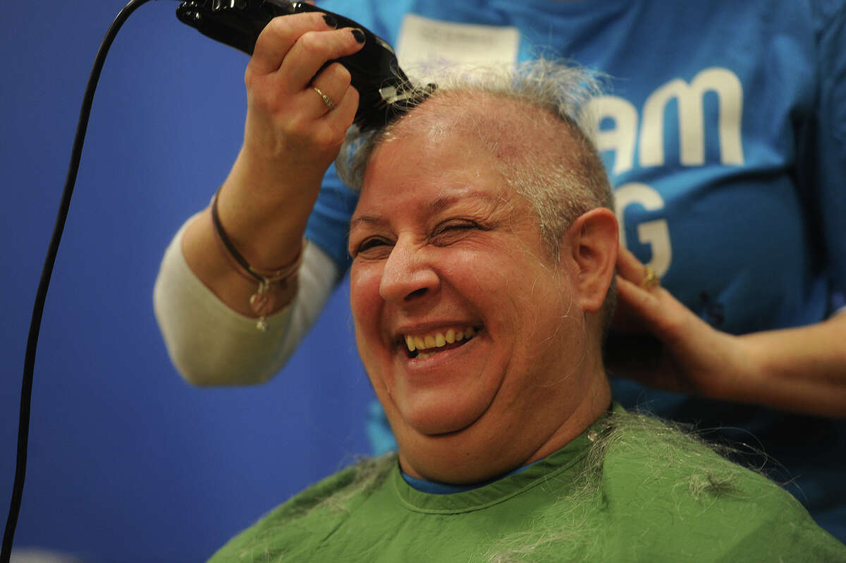 Bunnell High School health teacher Karen Marino smiles as she submits to having her head shaved during the Brave the Shave St. Baldrick's fundraiser at the school in Stratford, Conn. on Sunday, March 15, 2015. St. Baldrick's events raise money in support of childhood cancer research.