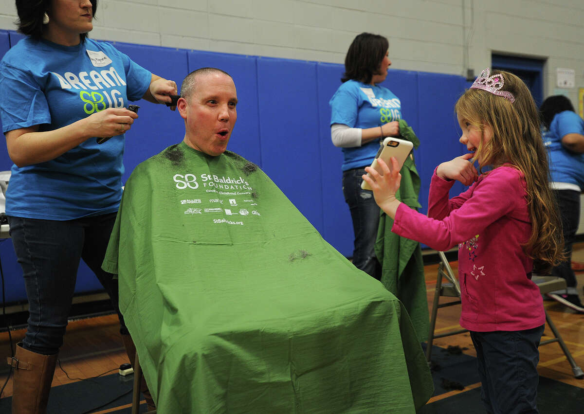 Bunnell High School Assistant Principal Christopher Koch reacts as his daughter Savannah, 5, shows him a picture of his shaved head at the Brave the Shave St. Baldrick's fundraiser at the school in Stratford, Conn. on Sunday, March 15, 2015. St. Baldrick's events raise money in support of childhood cancer research.