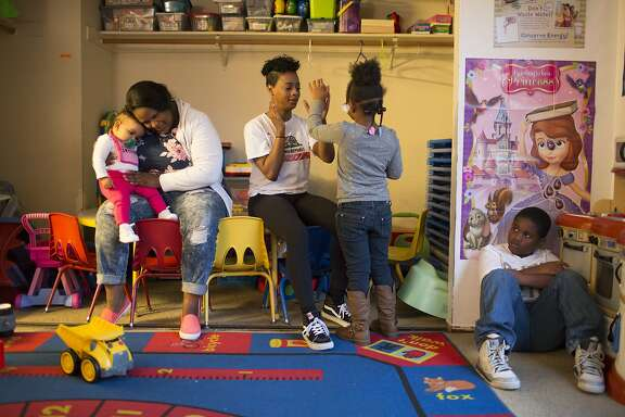 From left to right, Gabrielle Meeks, 9 months, Dawnielle Wright, 30, Brandeja Guinn, 17, Johanna Kelly, 4, and Jahmere Kelly, 9, play at Rose's Day Care in Oakland, Calif. on Monday, March 9, 2015. Cost for child care has risen at Rose's Day Care after the minimum wage increase.
