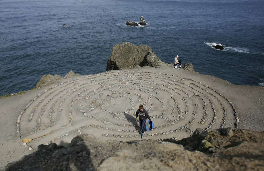 After being away on vacation, Colleen Yerge, known as the keeper of the Lands End Labyrinth, fixes up the labyrinth in San Francisco, Calif. Photo: Mike Kepka, The Chronicle