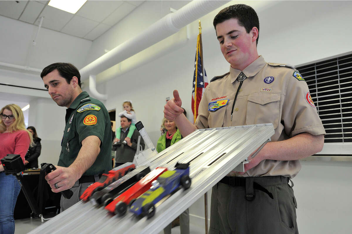 Kevin Piro releases the pinewood cars from the starting gate during the 2015 Greenwich Council Cub Scout Pinewood Derby Championship at Miller Motorcars in Greenwich, Conn., on Sunday, March 15, 2015. The top three racers from each Cub Sout pack of Greenwich's 10 packs competed Sunday for the top spot town-wide.