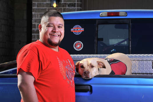 Juan Alonzo-Miranda with his service dog Goldie in front of their far West Side home. Alonzo-Miranda, 33, has sued Schlumberger Technology for back pay, compensatory damages for mental anguish, and unspecified punitive damages. Compensatory damages are capped at $300,000 by law. Photo: Robin Jerstad /San Antonio Express-News