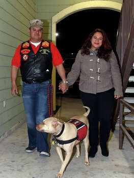 Juan Alonzo-Miranda and his wife, Ilsa Alonzo, walk with their dog Goldie at home on Nov. 26, 2013. Photo: Express-News File Photo