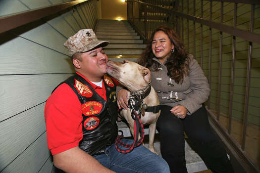 Juan Alonzo-Miranda sits with his service dog Goldie and his wife, Ilsa Alonzo, in November 2013. Alonzo-Miranda has sued Schlumberger Technology; the two sides are set to square off Monday in a San Antonio courtroom. Photo: Express-News File Photo
