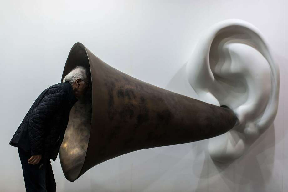 """A visitor peers into US artist John Baldessari's """"Beethoven's Trumpet (With Ear) Opus # 133"""" at the Art Basel fair in Hong Kong on March 15, 2015. Hong Kong's biggest art fair, Art Basel, opened its doors with thousands of visitors expected for a city-wide canvas of creativity and commerce. Photo: Anthony Wallace, AFP / Getty Images"""