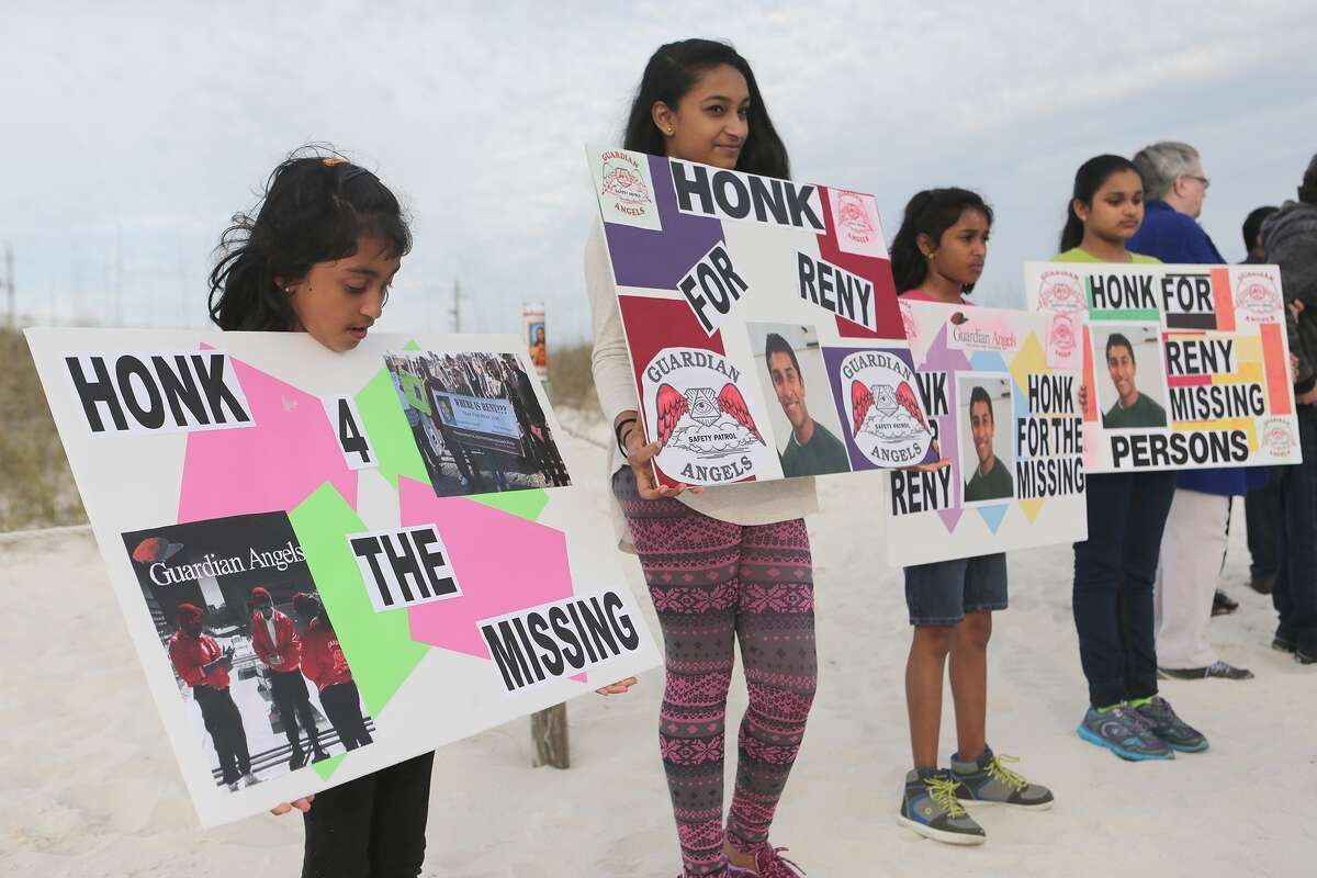 Sabina Mathew, 9, left, holds a sign with others during the vigil marking the one-year anniversary of the disappearance of Reny Jose on Saturday, March 14, 2015, in Panama City Beach, Fla.