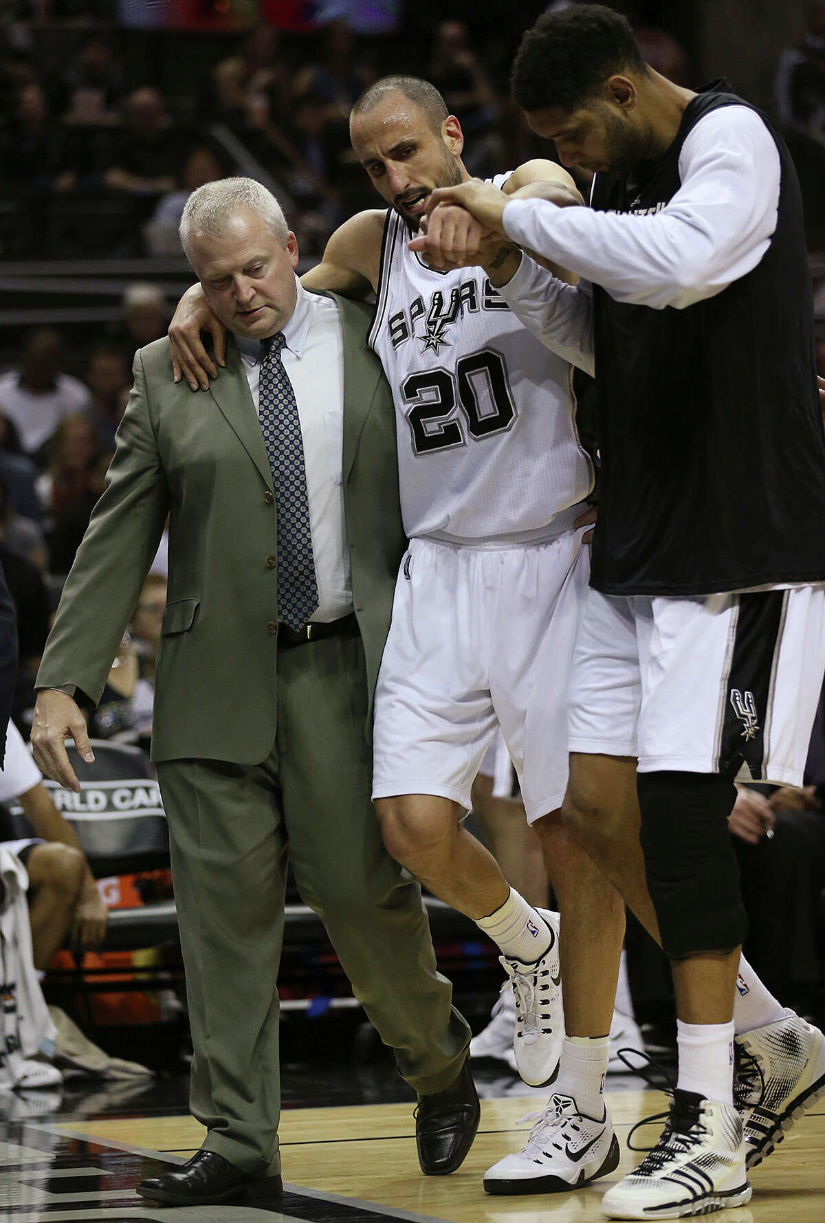 The Spurs' Manu Ginobili is helped off the court by head athletic trainer Will Sevening and Tim Duncan during the second half at the AT&T Center on March 15, 2015.