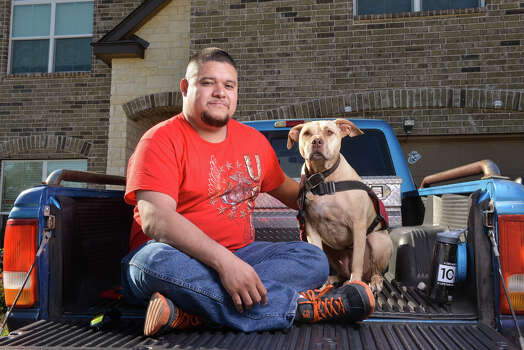 Juan Alonzo-Miranda with his service dog Goldie in front of their far west side home. Alonzo-Miranda sued Schlumberger Technologies Corp. alleging it violated the Americans with Disabilities Act by not allowing Goldie at his job to help him cope with Post Traumatic Stress Disorder. Photo: Robin Jerstad, San Antonio Express-News