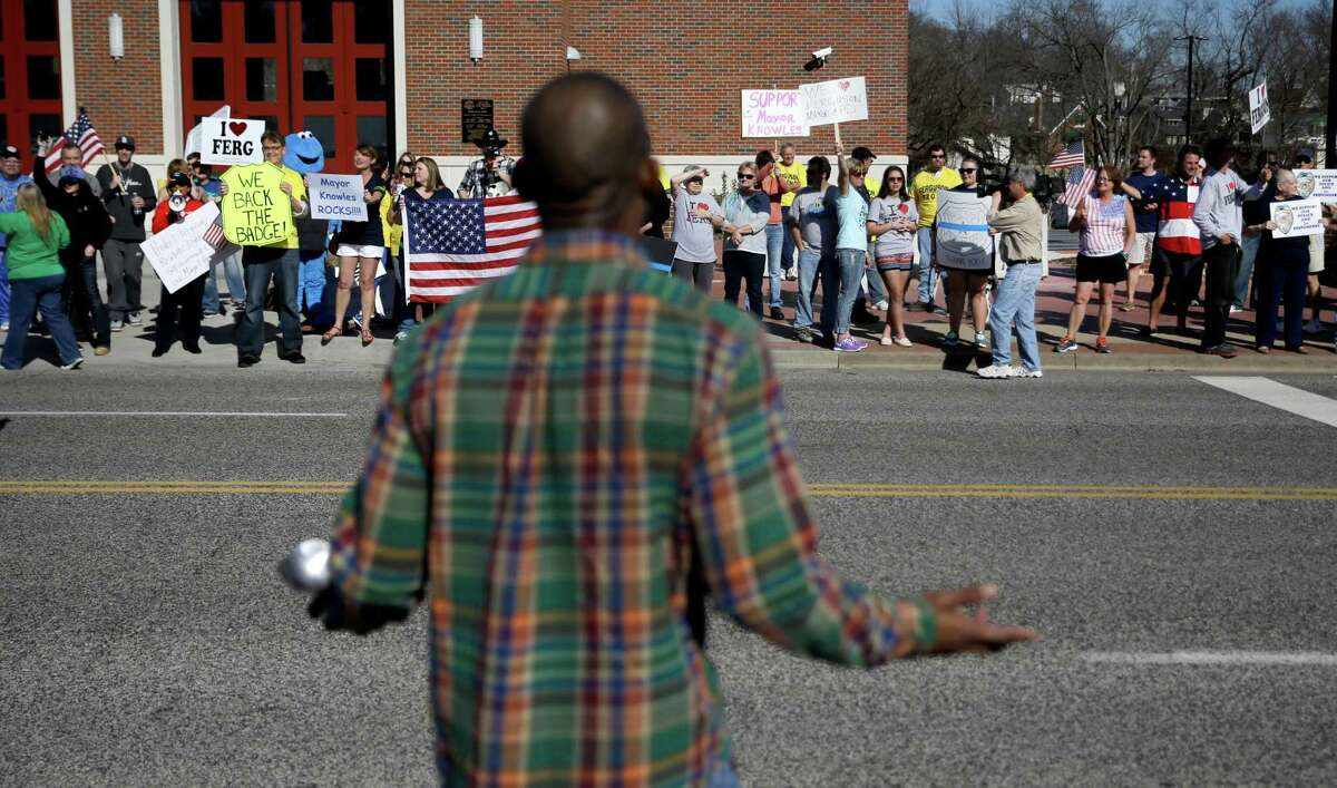 Counter demonstrator Maldon Moffitt, foreground, yells from across the street at pro-police demonstrators outside the Ferguson Police Department Sunday, March 15, 2015, in Ferguson, Mo. (AP Photo/Jeff Roberson) ORG XMIT: MOJR115