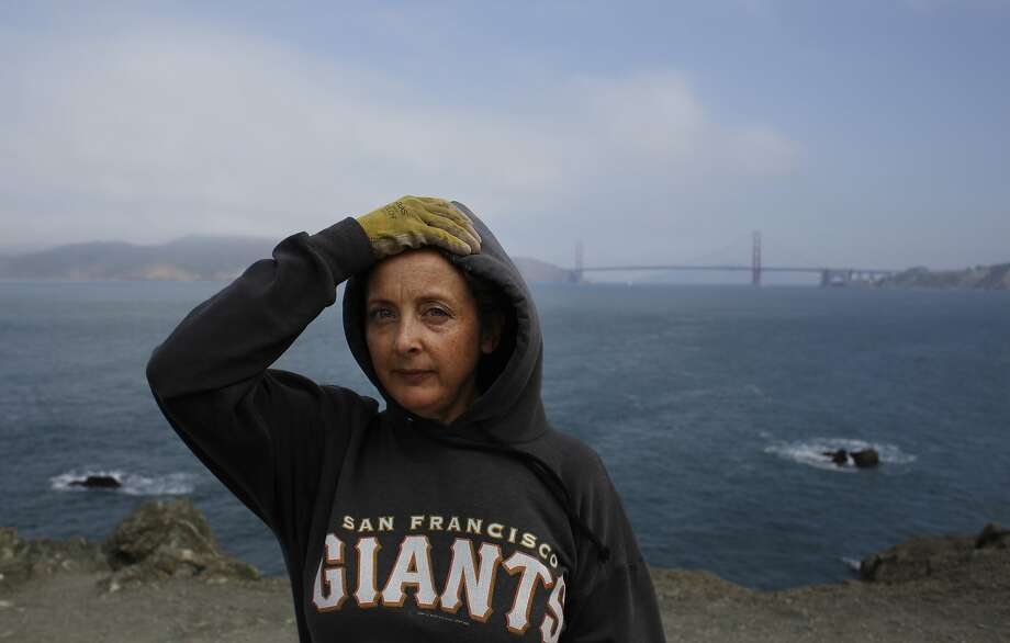 Yerge adjusts her hood as the fog flows in at the cliffside site of the labyrinth, overlooking the Pacific. Photo: Mike Kepka, The Chronicle