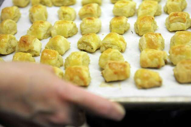 Sue Kimball from Clifton Park, a member of the Congregation Gates of Heaven, pulls out a tray of knishes from the oven on Sunday, March 15, 2015, in Schenectady, N.Y.  Members of the synagogue are working to prepare food for their 12th annual Jewish Food Festival which will be held on Sunday, March 22nd from noon to 3:00pm.  (Paul Buckowski / Times Union) Photo: PAUL BUCKOWSKI / 00031031A