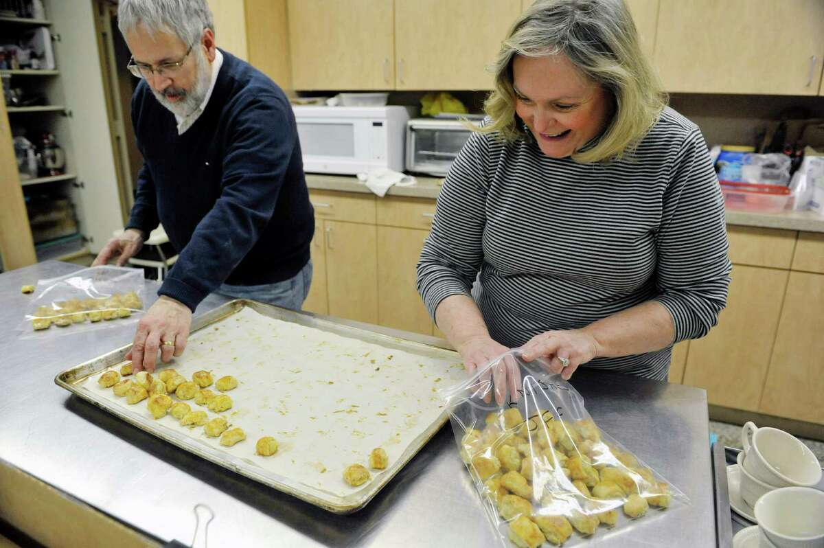 Congregation Gates of Heaven members Peter Kopcha of Niskayuna and Yetta Fox of Clifton Park place knishes into bags for storage on Sunday, March 15, 2015, in Schenectady, N.Y. (Paul Buckowski / Times Union)