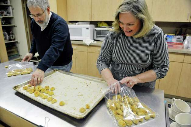 Congregation Gates of Heaven members Peter Kopcha of Niskayuna and Yetta Fox of Clifton Park place knishes into bags for storage on Sunday, March 15, 2015, in Schenectady, N.Y.  (Paul Buckowski / Times Union) Photo: PAUL BUCKOWSKI / 00031031A
