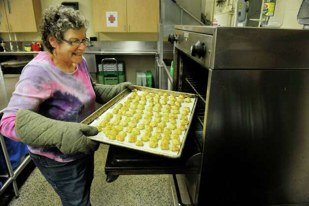 Sue Kimball from Clifton Park, and a member of the Congregation Gates of Heaven, pulls out a tray of knishes from the oven on Sunday, March 15, 2015, in Schenectady, N.Y.  Members of the synagogue are working to prepare food for their 12th annual Jewish Food Festival which will be held on Sunday, March 22nd from noon to 3:00pm.  Peter Kopcha, chair of the festival, said that the event gives the synagogue members a chance to share their Jewish culture with guests and the community at large through food.  (Paul Buckowski / Times Union) Photo: PAUL BUCKOWSKI / 00031031A