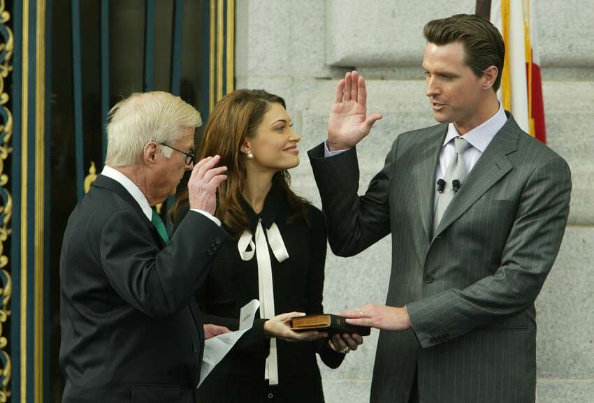 Gavin Newsom takes the oath of Office of Mayor from his father Judge William Newsom as his wife Kimberly Guilfoyle Newsom holds the bible.
