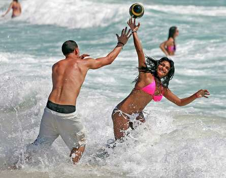 Mike Sierra, 21, and Larissa Macko, 21, spring breakers from the University of Central Florida, play ball on South Beach on Tuesday, March 10, 2015 in Miami Beach, Fla. Photo: Al Diaz, AP / The Miami Herald